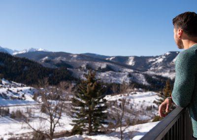 man overlooking snowy mountains