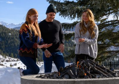 friends warming their hands over a fire pit
