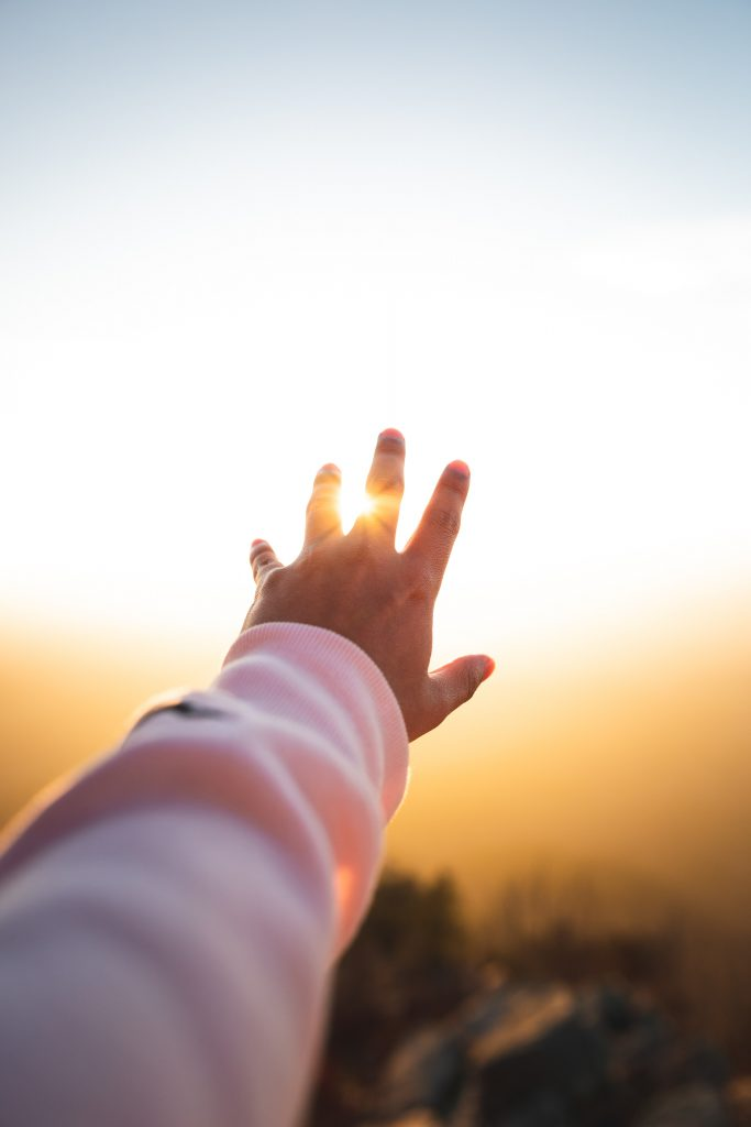 A hand reaching out to the sun over the horizon.