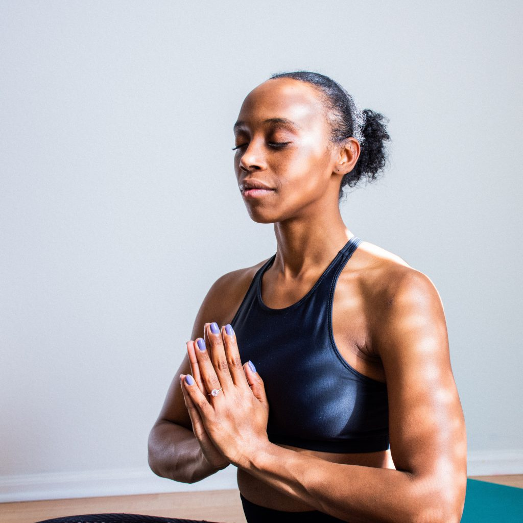 A woman meditating with her palms pressed together, eyes closed, seated and relaxed.