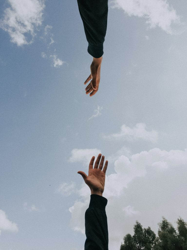 Two hands reaching towards each other across a background of the sky.