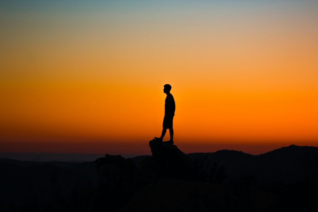 Silhouette of a man standing on an overlook with an orange fading sky in the background.
