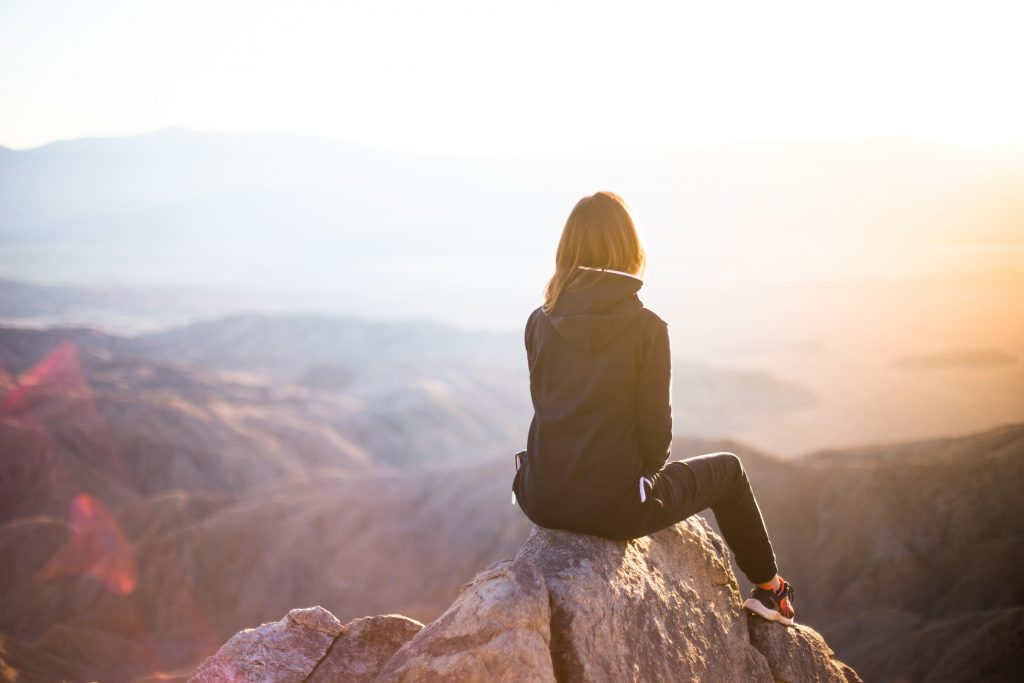 A woman sits on the precipice of a mountain, overlooking the valley below as the sun sets.