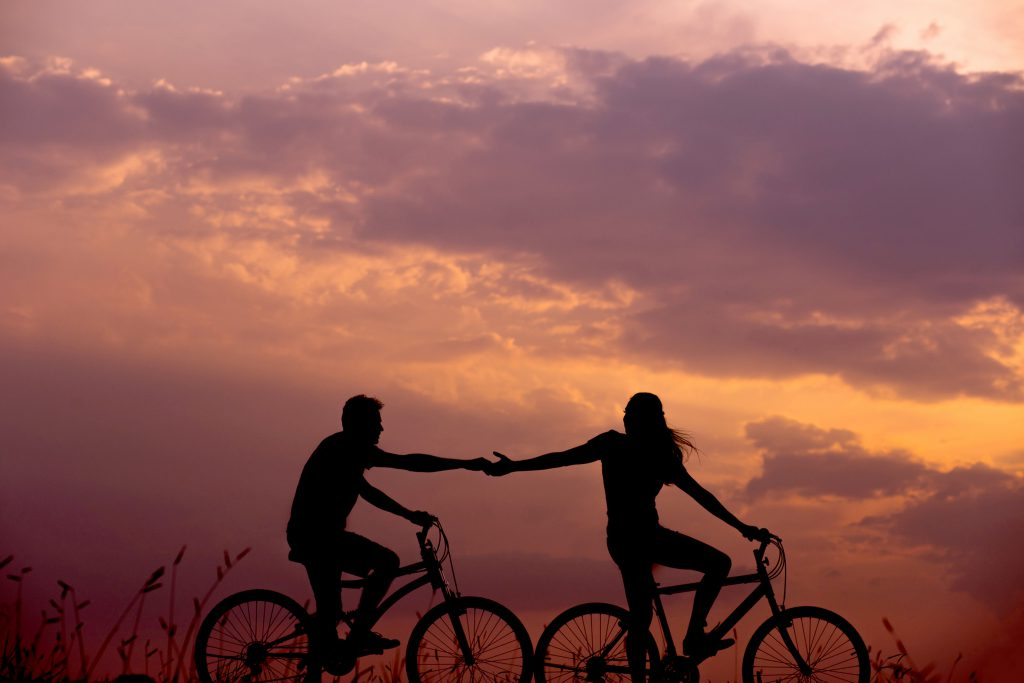 The silhouette of two people riding bikes with hands outstretched towards each other and a twilight sunset in the background.