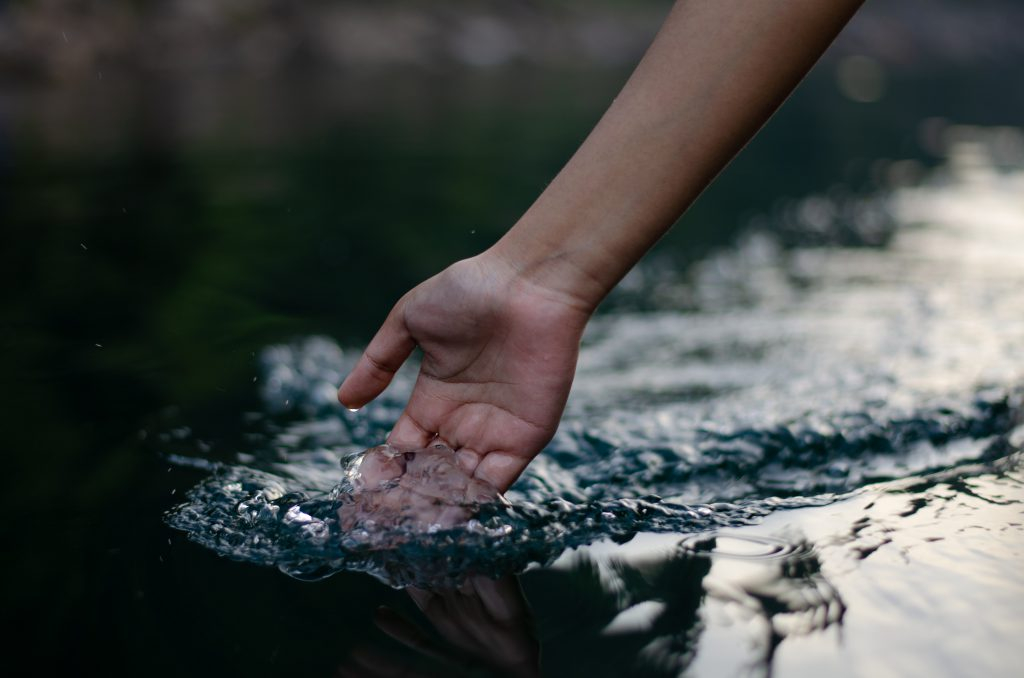 A hand dips into the water as a boat glides over a river.