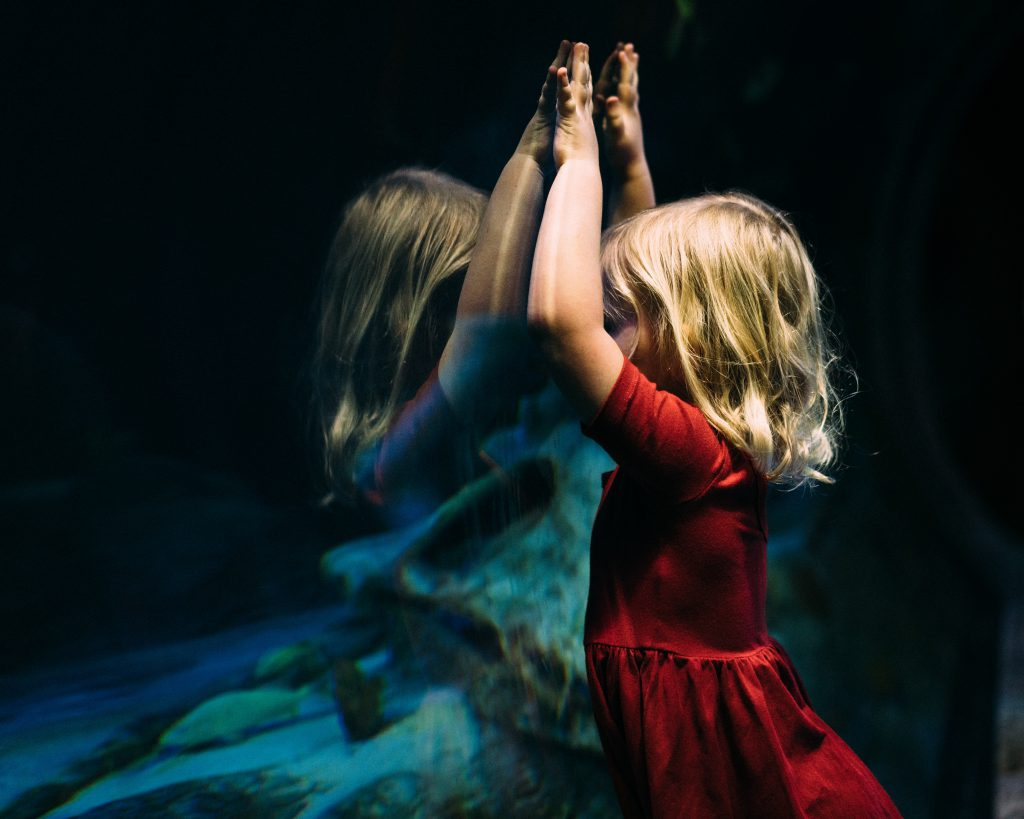 A little girl stands at the glass of an aquarium with her arms raised overhead.